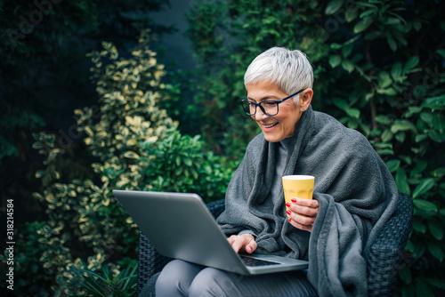 Leinwand Poster Smiling senior businesswoman using laptop in the garden, portrait