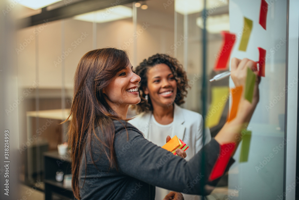 Fototapeta Smiling businesswoman brainstorming with adhesive notes on a glass wall in the office.