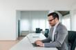 Leinwanddruck Bild - Business portrait of a handsome man in formal wear working on laptop, side view.