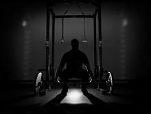 Full Length Of Silhouette Teenage Boy Holding Barbell In Darkroom