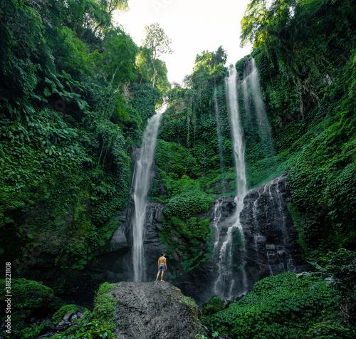 Obrazy dżungla   man-in-at-the-sekumpul-waterfalls-in-jungles-on-bali-island-indonesia-bali-travel-concept-banner