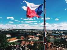 Czech Flag Waving By Cityscape Against Sky