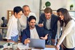 Group of business workers smiling happy and confident. One of them sitting and partners standing around. Working together with smile on face looking at the laptop at the office