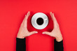Leinwanddruck Bild - Hands holds a cup of coffee isolated on red background