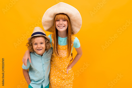Beautiful girl with red hair has fun with her little brother Canvas Print