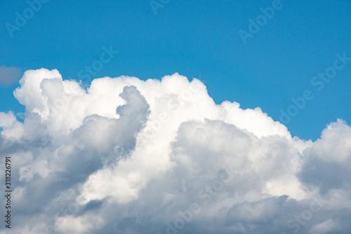Fotografie, Tablou Luminous clouds set against a dark blue sky in the sun