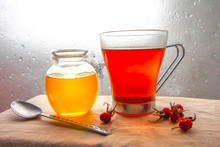 A Jar Of Honey, A Glass Of Tea With A Spoon And Hips Of Wild Rose Standing Near The Window Glass With Raindrops. Closeup