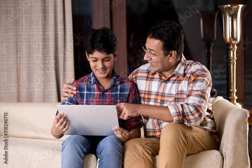Father and son astonished on receiving good news using laptop Canvas-taulu