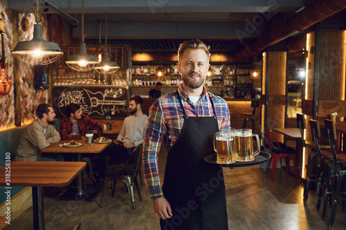 Fotografía Bearded waiter with a tray of glasses of beer against the background of a pub ba