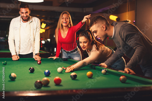 Group of friends play billiards at night out Fotobehang