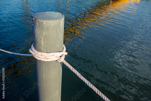 Fotografie, Obraz A mooring bollard entwined with a mooring rope at port
