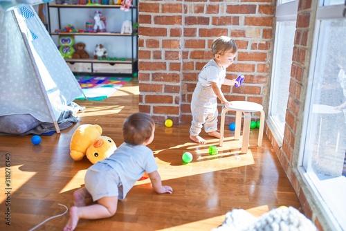 Obraz Beautiful toddlers playing around lots of toys at kindergarten - fototapety do salonu