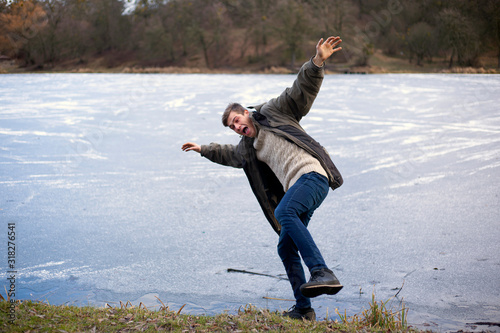 the wind blows away a person and he falls on a barely winter frozen lake on thin ice Wallpaper Mural