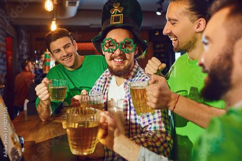 Fototapeta Happy friends celebrating St. Patrick's Day in a bar. obraz