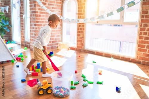 Obraz Beautiful blonde toddler playing tennis holding racket around lots of toys at kindergarten - fototapety do salonu