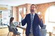 Middle age handsome businessman wearing glasses standing at the office crazy and mad shouting and yelling with aggressive expression and arms raised. Frustration concept.