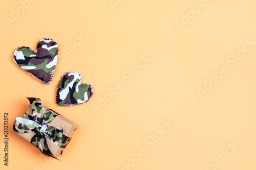 Fototapeta Gift box with camouflage ribbon and khaki hearts on yellow background