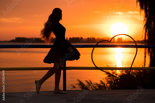 Photo Side view of back light of a woman silhouette breathing deep fresh air at warm sunrise in front of sun