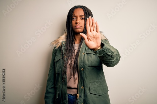 Photo Young african american woman wearing winter parka coat over isolated background doing stop sing with palm of the hand