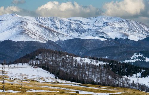 View of the mountains, covered with pine and snow, a cloud falls to the top Canvas Print