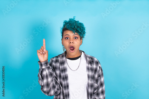 Photo isolated portrait of girl pointing on blue background with astonishment or surpr