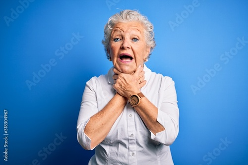Photo Senior beautiful woman wearing elegant shirt standing over isolated blue background shouting and suffocate because painful strangle