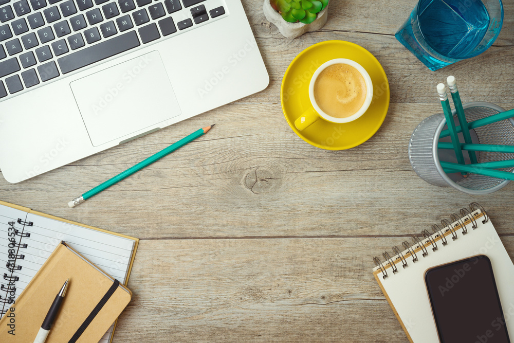 Fototapeta Office workplace table background with laptop computer, notebook and coffee cup.