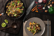 Asian food mix, in cooking pan and in plate, chopsticks, vegetables, top view on wooden table.
