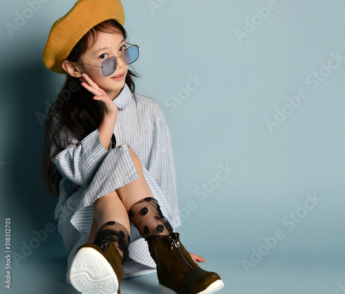 Little asian child in sunglasses, shirt dress, brown beret, boots. Smiling, posing sitting on blue background. Close up Wall mural