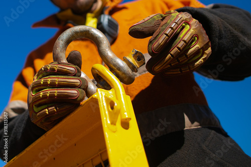Photo Close up rigger high risk worker wearing safety heavy duty glove, safety helmet