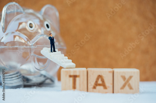 Photo Word block TAX with piggy bank