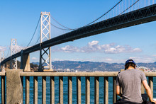 Rear View Of Man Standing By Bay Bridge Over San Francisco Bay Against Sky