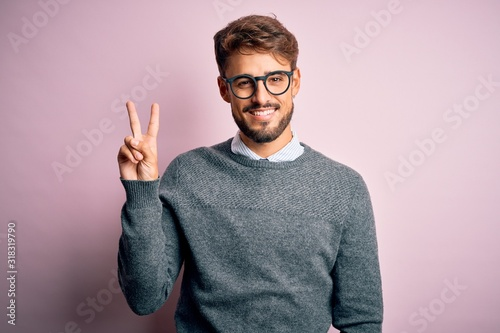 Young handsome man with beard wearing glasses and sweater standing over pink background showing and pointing up with fingers number two while smiling confident and happy.