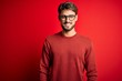Young handsome man with beard wearing glasses and sweater standing over red background with a happy and cool smile on face. Lucky person.