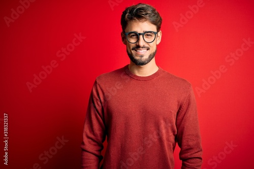 Fototapeta Young handsome man with beard wearing glasses and sweater standing over red background with a happy and cool smile on face. Lucky person. obraz