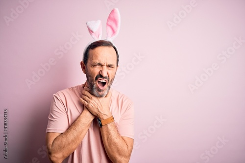 Middle age hoary man wearing bunny ears standing over isolated pink background shouting and suffocate because painful strangle Wallpaper Mural