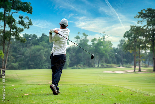 Golfer hitting golf shot with club on course while on summer vacation Fototapete