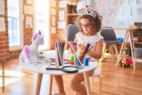 Beautiful toddler wearing glasses and princess crown sitting drawing using paper and marker pen at kindergarten