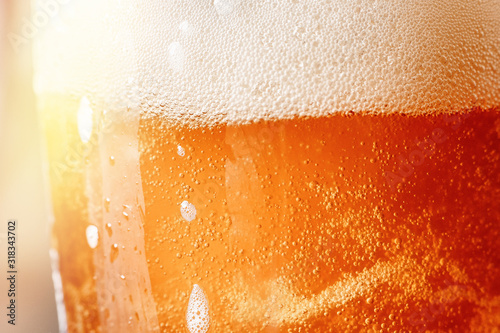 Close up gold background texture of yellow lager beer with froth and bubbles ...
