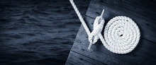 Boat Rope Secured To Cleat On Wooden Dock With Dark Water Below