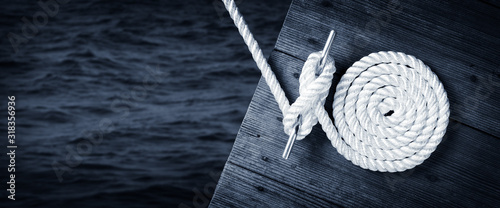 Fotografia Boat Rope Secured To Cleat On Wooden Dock With Dark Water Below