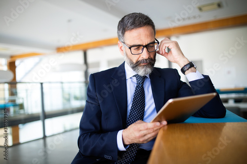 Cuadros en Lienzo Mature handsome business man using a digital tablet at office