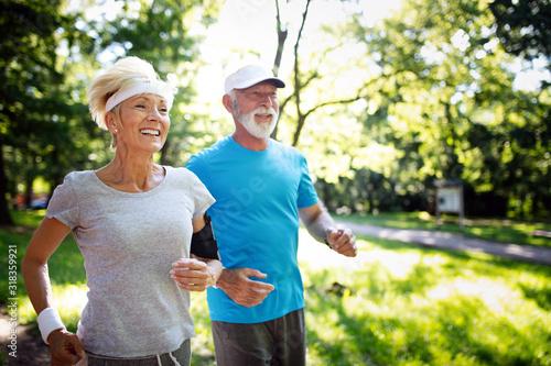 Beautiful mature couple jogging in nature living healthy Fototapete