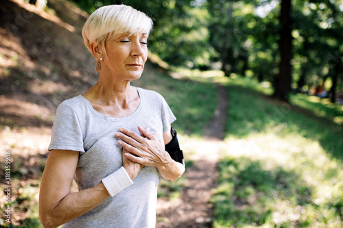 Leinwand Poster Senior woman with chest pain suffering from heart attack during jogging
