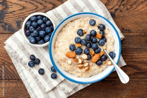Blueberry almond oatmeal porridge in bowl on a wooden table background, top view. Healthy food, clean eating concept