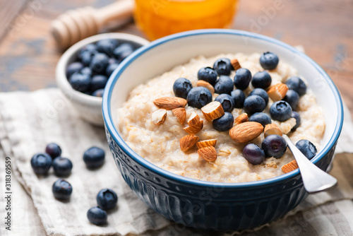 Obraz Oatmeal with blueberries and almonds in blue ceramic bowl on a wooden table. Closeup view of healthy breakfast food, vegan vegetarian meal - fototapety do salonu
