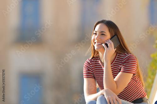 Obraz Happy girl talking on mobile phone sitting outdoors - fototapety do salonu
