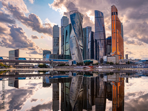 obraz PCV Urban landscape of steel color. Skyscrapers of Moscow are reflected in the water. Moskva-city. Tall buildings and gray clouds. Reflection. Panorama of modern Moscow.