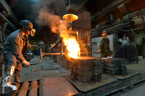 Obraz workers in a foundry casting a metal workpiece - safety at work and teamwork - fototapety do salonu