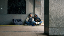 Homeless People Ask For Alms Sitting On The Sidewalk Against The Wall
